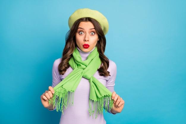Фотография фанк-путешественницы, держащей шарф за руки, не уверенная в стиле, хочу переодеться, носить зеленый берет, шляпу, фиолетовую водолазку, изолированную ярко-синюю стену