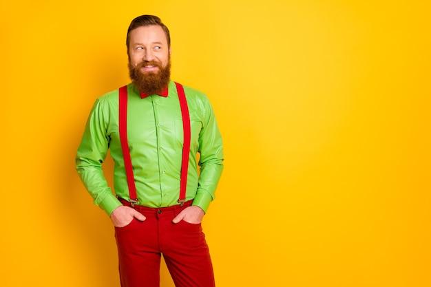 Фото забавного привлекательного парня, зубастых улыбок, элегантная одежда, взгляд сбоку, пустое пространство, одежда ярко-зеленая, рубашка, красные подтяжки, галстук-бабочка, штаны, изолированные яркие цвета