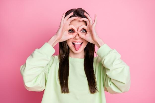 우스꽝스러운 매력적인 여성의 스트레이트 헤어스타일의 재미있는 소녀스러운 혀를 입으로 내밀고 장난스러운 분위기를 연출하는 사진은 손에 손가락 안경을 착용하게 하는 캐주얼한 스웨터 풀오버 격리된 분홍색 배경