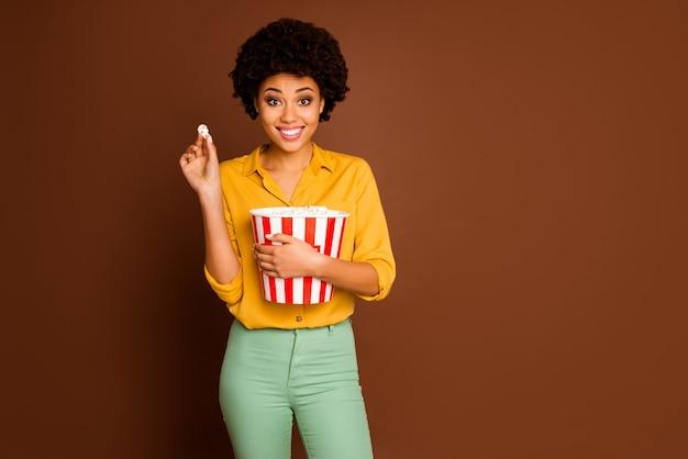 Фото забавной очаровательной темнокожей кудрявой дамы с ведром для попкорна, которая ест кукурузу и смотрит любимое телешоу, в желтой рубашке, в зеленых штанах, изолированном коричневом цвете