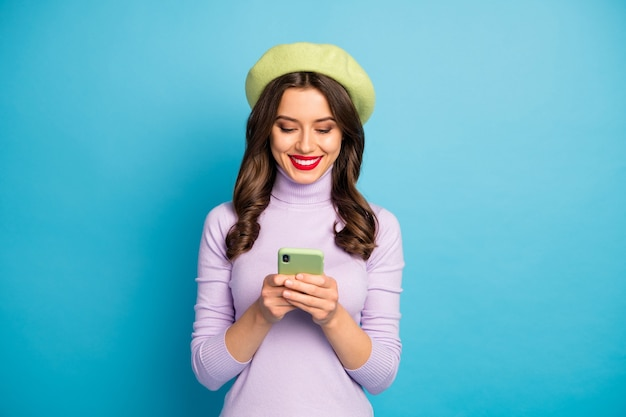 電話の手を握ってメッセージを書いている面白い魅力的な女性の写真親友が旅行している紫色のジャンパー緑色のベレー帽キャップ孤立した青い色の壁を着用してください