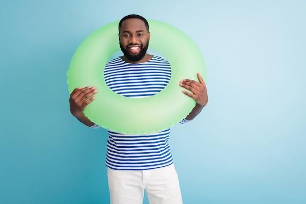 面白い陽気な暗い肌の男の写真は首の周りに緑の救命浮環を保持します準備ができて泳ぐ海の海の旅行者良い気分晴れた日着用ストライプセーラーシャツ孤立した青い色の壁