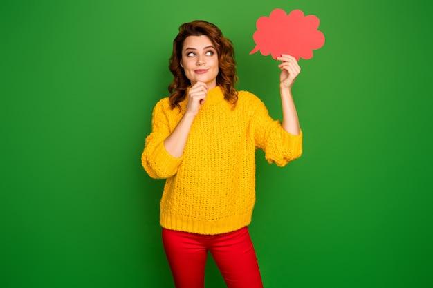 面白い陽気な波状の女性の写真は、興味を持って考えている紙の心の雲を保持します空のスペースを調べます狡猾な目は黄色のニットセーター赤いズボン孤立した緑色の壁を着用します