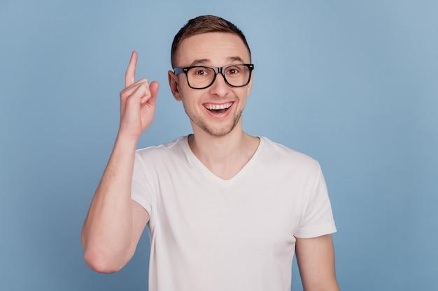 Фотография смешного умного молодого возбужденного человека, указывающего пальцем, имеющего гениальную идею, изолировала синий цвет фона