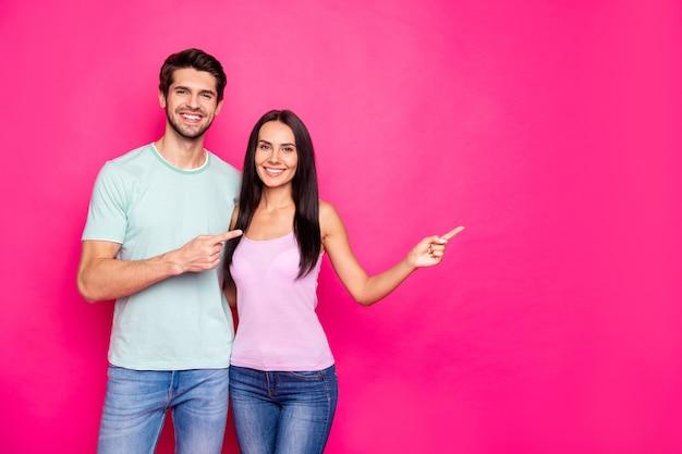 ブラックフライデーの買い物をアドバイスする空のスペースに指を示す面白いカップルの男と女の写真は、鮮やかなピンク色の背景を分離したカジュアルな服を着る