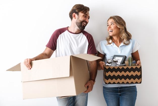 白い壁の上に隔離されたお互いを見ながら段ボール箱を保持しているカジュアルな服を着た面白いカップルの写真