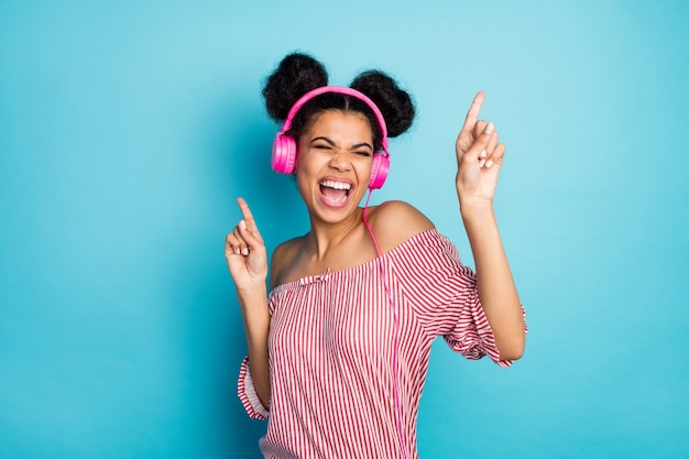 재미 있은 미친 어두운 피부 아가씨의 사진 음악 듣기 현대 이어폰 좋아하는 노래를 부르고 손가락을 올리십시오 춤 착용 유행 빨간색 흰색 줄무늬 셔츠 오프 어깨 절연 파란색 벽