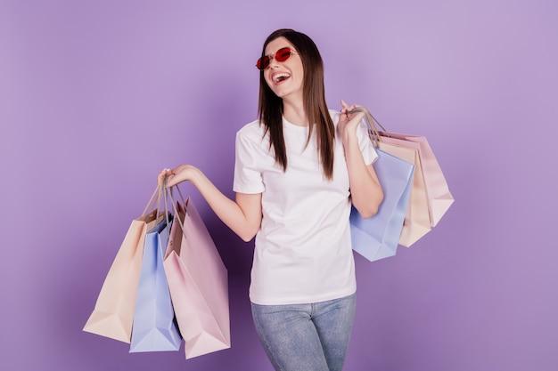 Фото смешной сумасшедшей дамы несут пакеты с покупками на изолированном фиолетовом фоне