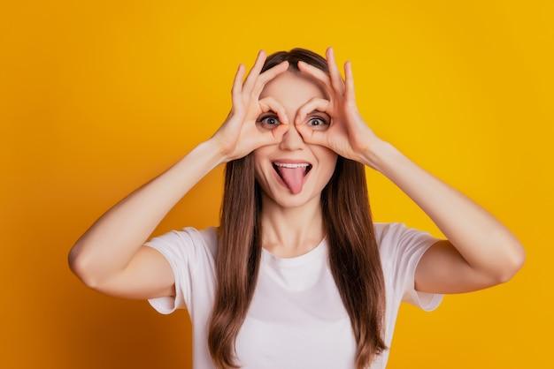 웃긴 미친 여자의 사진 두 개의 oky 표시가 눈을 덮고 혀가 튀어나와 노란색 배경에 흰색 티셔츠를 입고 포즈를 취합니다
