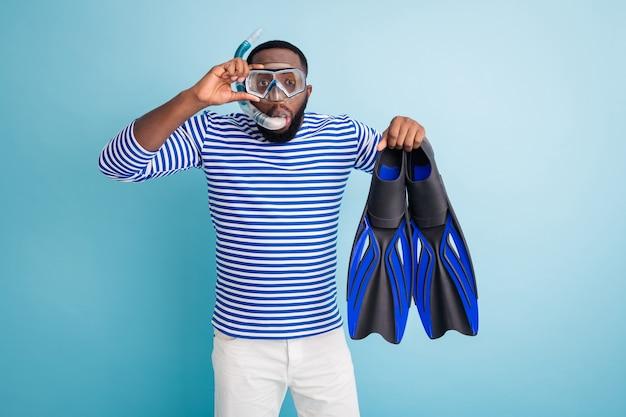 面白い暗い肌の男の写真は、頭に足ひれチューブゴーグルマスクを保持し、沈み始めることに興奮しています白いサンキャップストライプセーラーシャツショーツ孤立した青い色の壁
