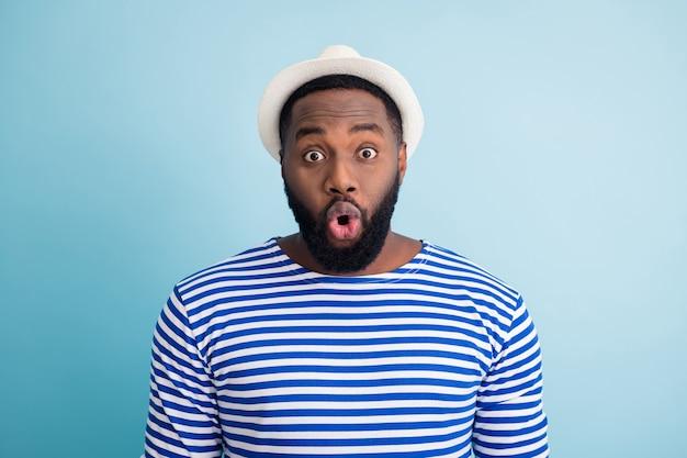 面白い暗い肌の男の写真は海外で休む自由な時間をリゾートで過ごす低ショッピングセンターの価格を参照してください口を開けて白いサンキャップストライプセーラーシャツ孤立した青い色の壁