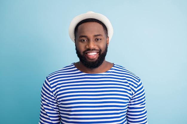 面白い暗い肌の男の旅行者の歯を見せる笑顔の写真は海外で自由な時間を過ごします日当たりの良いリゾートは白い太陽の帽子の縞模様のセーラーシャツを着用します孤立した青い色の壁