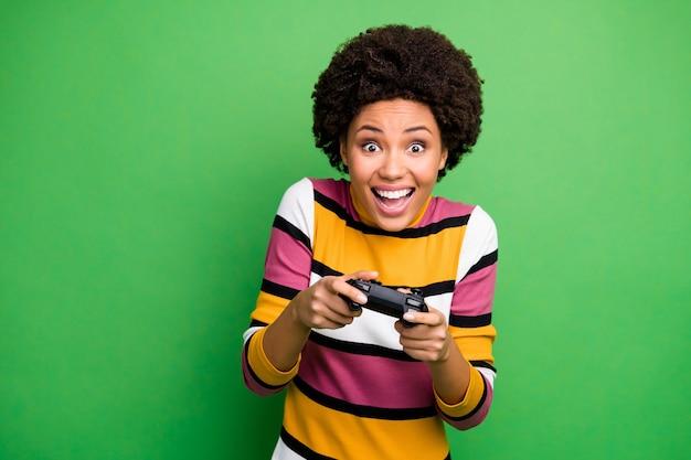 Фото смешной темнокожей дамы с хорошим настроением, играющей в видеоигры, увлеченного геймера, взволнованного, держите джойстик, руки в повседневном полосатом свитере