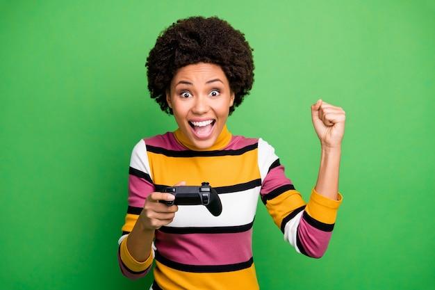Фотография смешной темнокожей дамы, играющей в видеоигры, увлеченного геймера, взволнованного, удерживающего джойстик, рука празднует победу, поднятие кулака, повседневный полосатый свитер