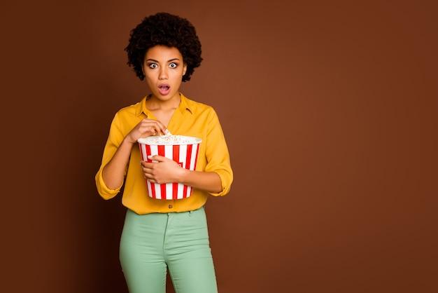 Фотография смешной темнокожей волнистой дамы, держащей ведро с попкорном, ест мозоли, смотрит страшный фильм, триллер, с открытым ртом, в желтой рубашке, в зеленых штанах, изолированном коричневом цвете