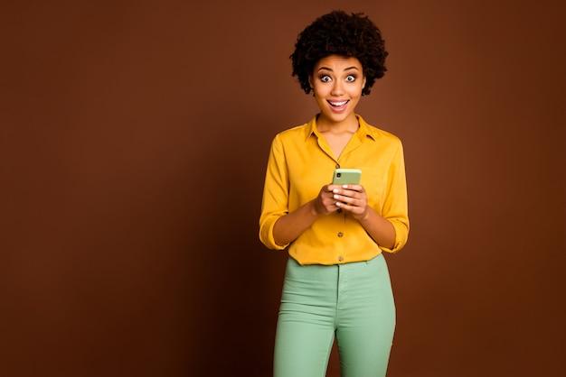 電話の手を握っている面白い暗い肌の波状の女性の写真インフルエンサー口を開けて肯定的なコメントを読む黄色のシャツを着る緑のズボン孤立した茶色の色