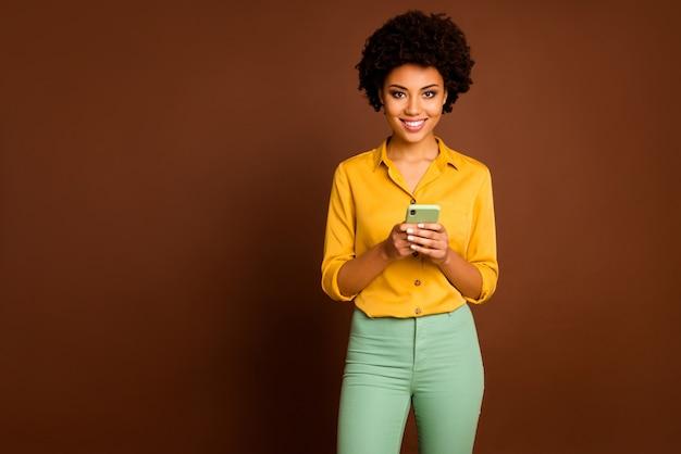 Фото смешной темнокожей волнистой дамы, держащей телефон в руках, влиятельный человек с открытым ртом, читайте положительные комментарии, носите желтую рубашку, зеленые брюки, изолированные коричневого цвета