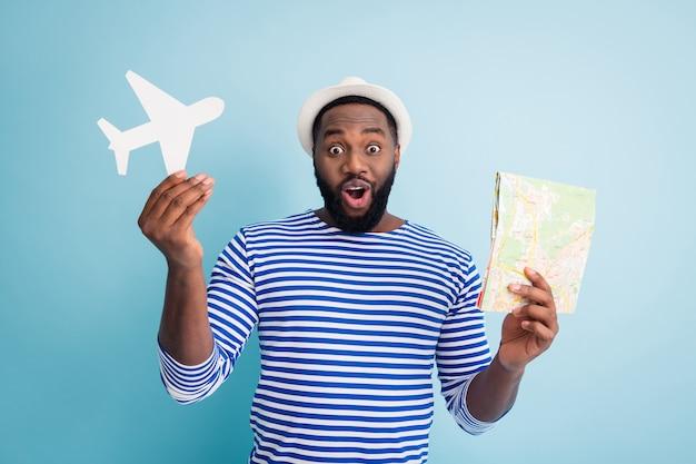面白い興奮した暗い肌の男の旅行者の写真は、紙の飛行機の地図を保持し、素敵な安い旅行のバリエーションを提供します白いサンキャップストライプセーラーシャツ孤立した青い色の壁