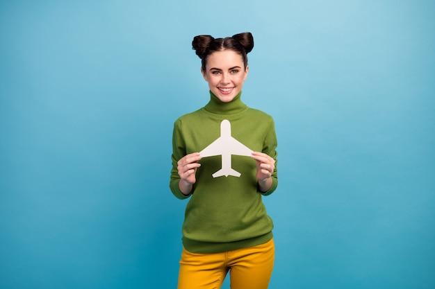 面白い興奮したきれいな女性の写真は紙飛行機中毒の旅行者を保持します安いツアー海外旅行を購入しますフライトウェア緑のタートルネック黄色のズボン孤立した青い色の壁