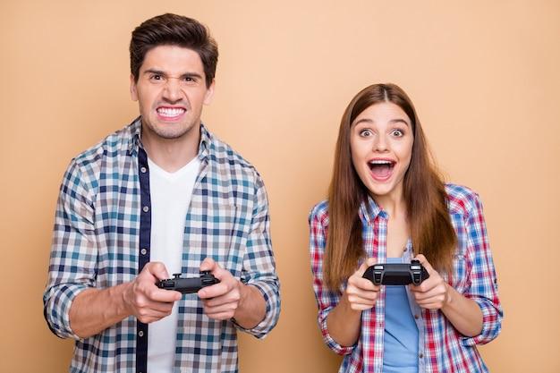 Фотография смешной фанковой пары из двух человек, играющих в видеоигры с подругой, побеждающей своего парня, улыбающегося от гнева, изолированного на бежевом пастельном цветном фоне