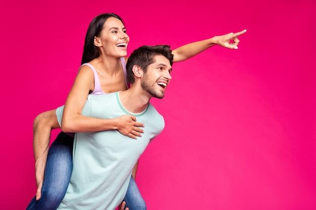 재미 있은 남자와 여자의 사진 들고 피기 백 찾고 빈 공간을 나타내는 손가락 예쁜 공원 캐주얼 옷을 입고 격리 된 생생한 핑크 컬러 배경