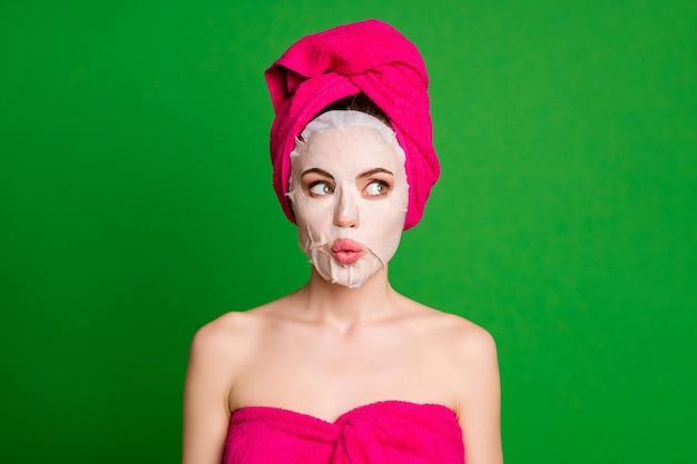 Фото смешной дамы нанести маску на лицо взгляд сбоку пустое пространство носить полотенца тело голова изолированный зеленый цвет фона