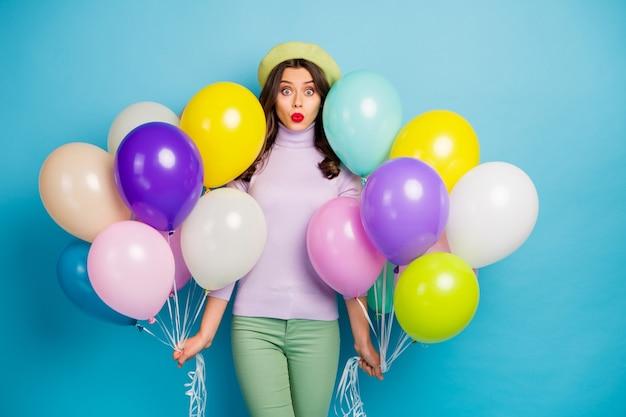 面白い女性の写真は多くのカラフルな気球を運ぶ予期しない驚きのパーティー口を開ける紫色のジャンパーベレー帽キャップ緑色のズボン孤立した青い色の壁