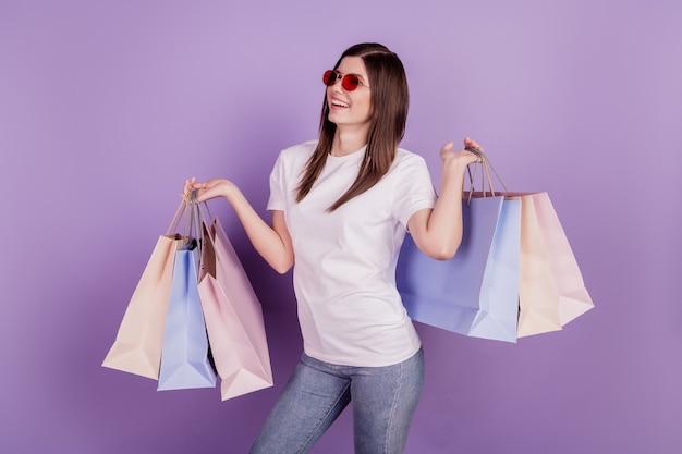 Фото смешной дамы несут пакеты с покупками, изолированные на фиолетовом фоне