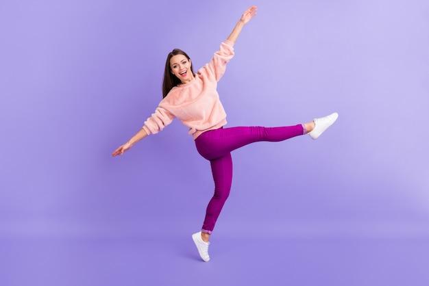 Фотография смешной леди танцует вечеринку носить меховой свитер кроссовки изолированы фиолетовый цвет фона