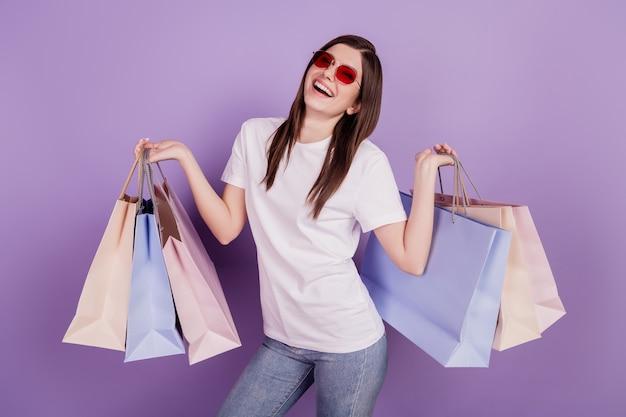 Фото смешной дамы наслаждается носить с собой пакеты с покупками, изолированные на фиолетовом фоне