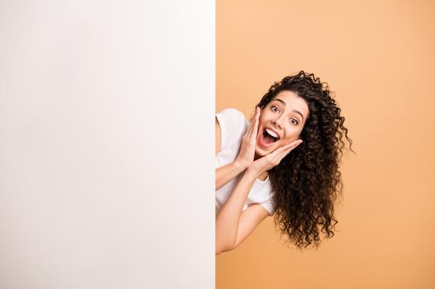 Фотография смешной дамы, держащей руки на щеках, читающей большой белый плакат, представляющего информацию о новизне, носить белую одежду, изолированный бежевый пастельный цвет фона