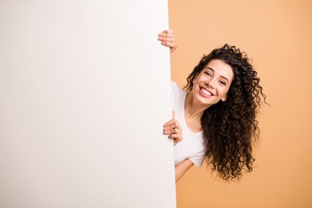 Фотография забавной дамы, держащей большой белый плакат, представляющего информацию о новинке, очаровательный промоутер носит белую одежду, изолированный бежевый пастельный цвет фона