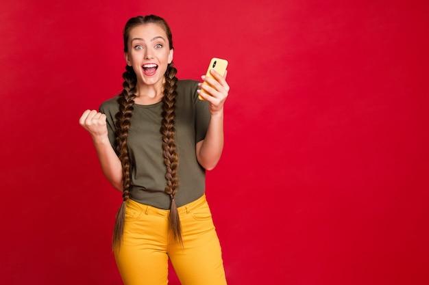 Фотография смешной дамы, держащей телефон за руки, празднующей новый стартап-проект, успешные инвестиции, повседневные желтые брюки, зеленая футболка, изолированный красный цвет фона