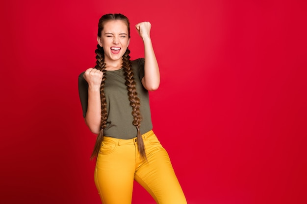 Фотография смешной дамы с длинными косами, поднимающими кулаки, празднуя лучшую футбольную команду-победитель, удивительный день, повседневная зеленая футболка, желтые брюки, изолированный красный цвет фона