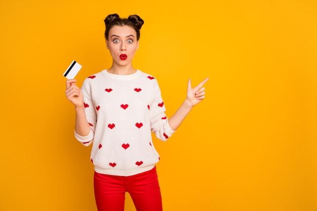 Фотография смешной дамы, показывающей новую пластиковую кредитную карту, указывая пальцем на пустое место, баннерная реклама, белый пуловер с рисунком сердец