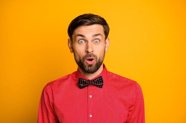 面白いマッチョな男の良い気分の写真は、目が黒い蝶ネクタイでスタイリッシュな赤いシャツを着ているとは思わない、予期しない驚きの口を開けて楽しむ