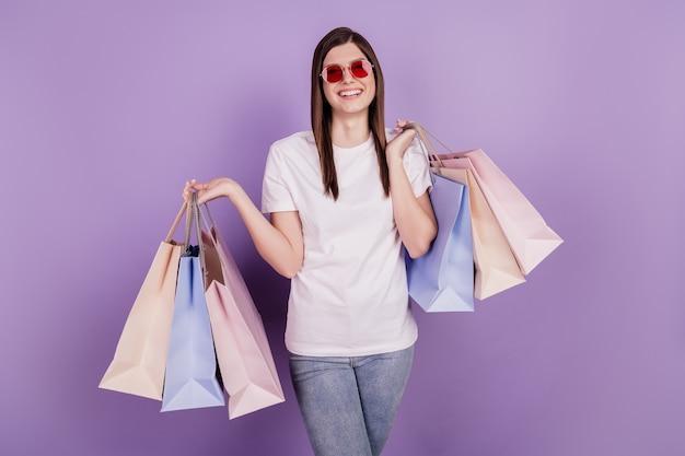 Фото смешной позитивной дамы несут пакеты с покупками на изолированном фиолетовом фоне
