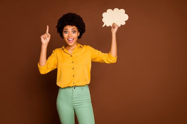 面白いかなり暗い肌の巻き毛の女性の写真は空の紙の雲のバナーポスターを保持します創造的な対話の答えのアイデアを着る黄色いシャツ緑のズボン孤立した茶色の色