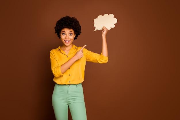 Фотография смешной красивой темнокожей кудрявой дамы, держащей пустой бумажный плакат с облаком, направляя палец на ее ответ диалог, в желтой рубашке, в зеленых штанах, изолированных коричневый цвет