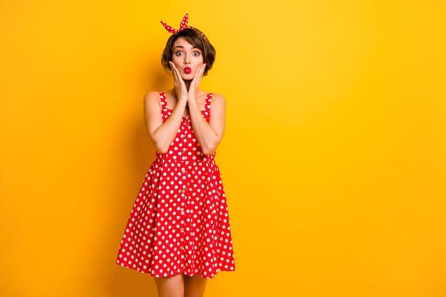 Фотография смешной симпатичной дамы, держащей руки на щеках, отправляющей воздушный поцелуй, кокетливая одежда для настроения, ретро-лето, красно-белое платье в горошек, ободок, изолированная ярко-желтая цветная стена
