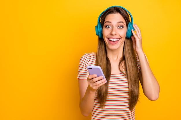 面白いきれいな女性の写真は電話を保持しますクールなワイヤレスイヤホンはラジオをオンにします愛の告白大喜びの着用カジュアルな縞模様のtシャツ分離された黄色の壁