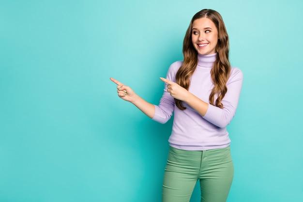 Фотография забавной симпатичной леди показывает, что пальцы выглядят пустым местом, предлагают новинку, цены на товары со скидкой, зависимый покупатель носит фиолетовый свитер зеленые брюки, изолированные пастельно-бирюзового цвета