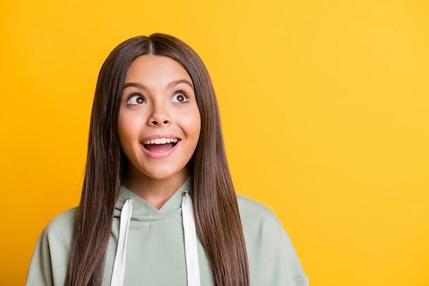 Фотография смешной блестящей школьницы в повседневной серой одежде, улыбающейся, глядя на пустое пространство, изолированный желтый цвет фона