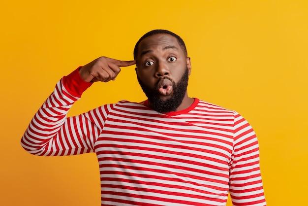 Фото смешного шокированного человека виска пальца глупая гримаса на желтом фоне