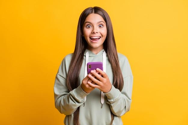 面白いショックを受けた女子高生の写真は、手をつないでカジュアルな灰色の服を着ています現代のガジェットは黄色の背景を分離しました