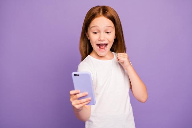 Фото смешной маленькой возбужденной рыжей девушки, держащей телефон, поднять кулак