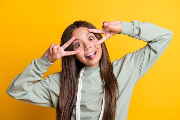 Фотография смешной милой школьницы в повседневной серой одежде, показывающей v-образный глаз, язык, изолированный желтый цвет фона
