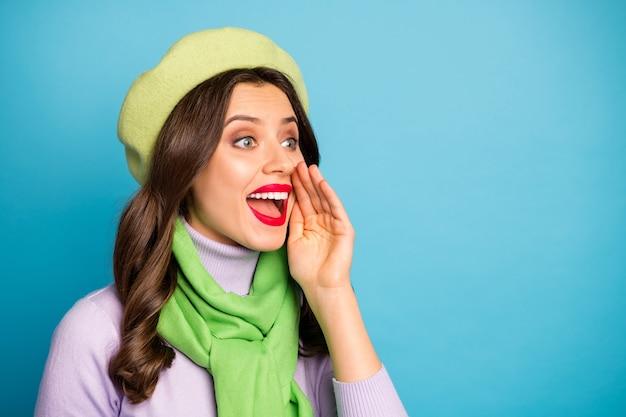 Фото смешной путешественницы леди держаться за руку возле рта кричать распродажа покупки секретное сообщение носить зеленый берет шляпа фиолетовый водолазка шарф изолированный синий цвет стены