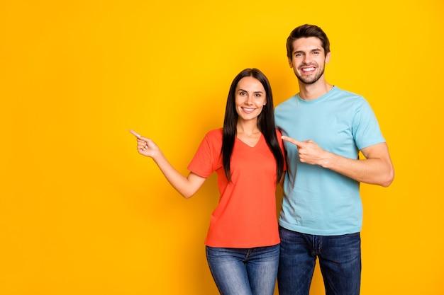 Фотография смешных двух человек пара парень и дама обнимаются направляя пальцы пустое пространство низкие цены шоппинг носить повседневные синие оранжевые футболки джинсы изолированные стены желтого цвета