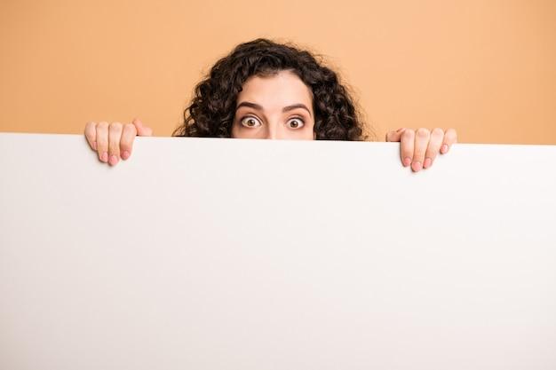 Фотография смешной волнистой дамы с большими глазами страха, держащими пальцы, большой белый плакат, представляющий информацию о новизне, шокирован изолированный бежевый пастельный цвет фона